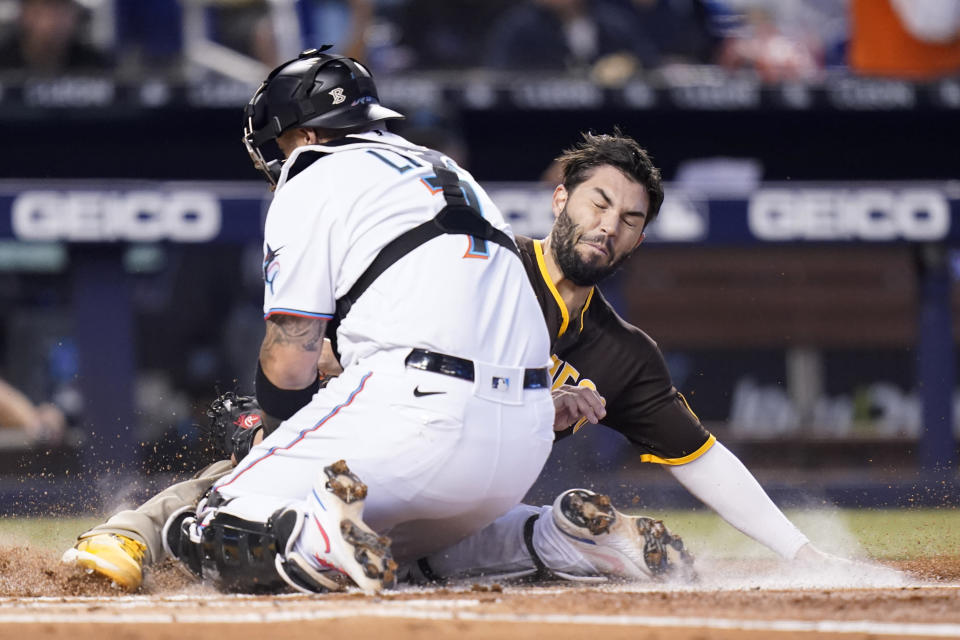 San Diego Padres' Eric Hosmer, right, is tagged out at the plate by Miami Marlins catcher Sandy Leon during the second inning of a baseball game, Sunday, July 25, 2021, in Miami. (AP Photo/Lynne Sladky)