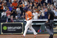 Houston Astros' Martin Maldonado (15) reacts as he crosses home plate in front of umpire Alan Porter, right, after his two-run home run during the fifth inning of a baseball game against the Texas Rangers, Friday, May 14, 2021, in Houston. (AP Photo/Michael Wyke)