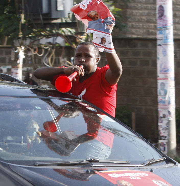 A supporter of Kenyan presidential candidate Uhuru Kenyatta celebrates what he perceive is an election win for him in Kikuyu town near Nairobi, Kenya Saturday, March 9, 2013. Kenya's election commission posted complete results early Saturday showing that Deputy Prime Minister Uhuru Kenyatta prevailed in the country's presidential elections by the slimmest of margins, winning 50.03 percent of the vote.(AP Photo/Sayyid Azim)