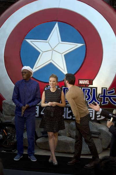 """In this Monday, March 24, 2014 photo, actress Scarlett Johansson stands between Samuel L. Jackson, left, and Chris Evans during a publicity event ahead of the April release of their movie """"Captain America: The Winter Soldier"""" in Beijing. Captain America and Spiderman are seeking to dominate the Chinese box office in the coming weeks, proving that U.S. patriotic superheroes can overcome China's leeriness of foreign films if they promise big money. Chinese authorities, wary of outside cultural influences and competition, restrict the number of foreign movies shown in the mainland's cinemas to 34 each year. (AP Photo/Ng Han Guan)"""