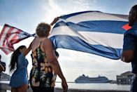 Cubans wave a US and a Cuban flag as the first US-to-Cuba cruise ship in decades arrives in the island nation on May 2, 2016 (AFP Photo/Adalberto Roque)