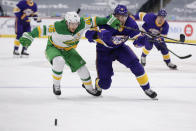 Los Angeles Kings right wing Alex Iafallo (19) and Minnesota Wild defenseman Jared Spurgeon (46) battle for the puck in the first period during an NHL hockey game, Saturday, Feb. 27, 2021, in St. Paul, Minn. (AP Photo/Andy Clayton-King)