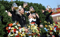 People lift glasses during a parade as part of the opening of the 186th 'Oktoberfest' beer festival in Munich, Germany, Saturday, Sept. 21, 2019. (AP Photo/Matthias Schrader)
