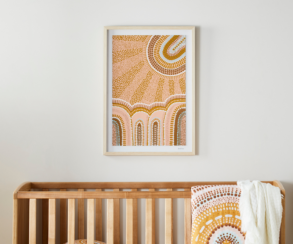 An indigenous dotted painting is framed on a white wall above a timber cot with a matching patterned blanket over the top of the cot.https://fave.co/3iwZUzc