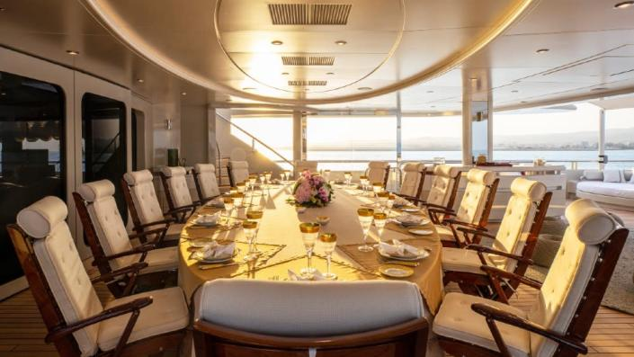 Who needs a formal dining room inside when there's a dining table for 14—with mirrored surface—in a protected area of the cockpit. - Credit: Courtesy Dynamiq/YachtShot