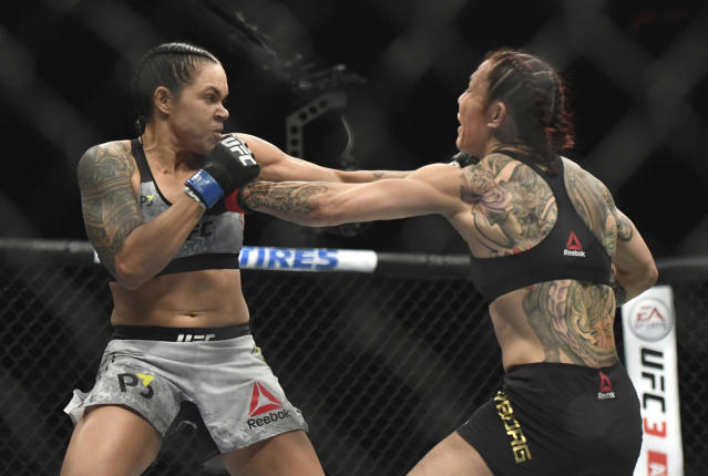 Amanda Nunues, left, lands a punch to Cris Cyborg during the first round of a featherweight title mixed martial arts bout at UFC 232, Saturday, Dec. 29, 2018, in Inglewood, Calif. (AP Photo/Kyusung Gong)