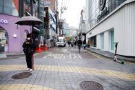A part time worker holds a banner promoting a cat cafe on an empty shopping street amid the coronavirus disease (COVID-19) pandemic in Seoul