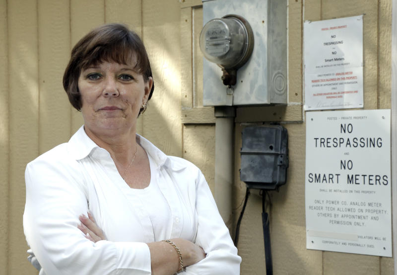 In this Friday, Aug. 24, 2012, photo, Thelma Taormina poses next to her old electric meter at her home in Houston. Taormina was involved in a confrontation last summer when a contractor for CenterPoint Energy had refused to leave her property without first installing a smart meter designed to remotely monitor her electricity usage. Nearly 6 million smart meters have been installed in Texas since a state law passed in 2005 authorized the state Public Utilities Commission to develop a smart meter deployment plan. Installation began three years later but opposition has gradually grown as word has spread about potential drawbacks. (AP Photo/David J. Phillip)