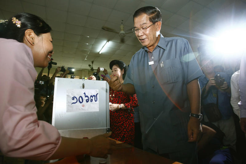 Cambodia's Prime Minister Hun Sen, foreground, looks at his inked finger after voting at a polling station in Takhmau town, south of Phnom Penh, Cambodia, Sunday, July 28, 2013. Hun Sen was among the early voters Sunday, casting his ballot shortly after the polls opened in a national election his party is expected to easily dominate. (AP Photo/Heng Sinith)