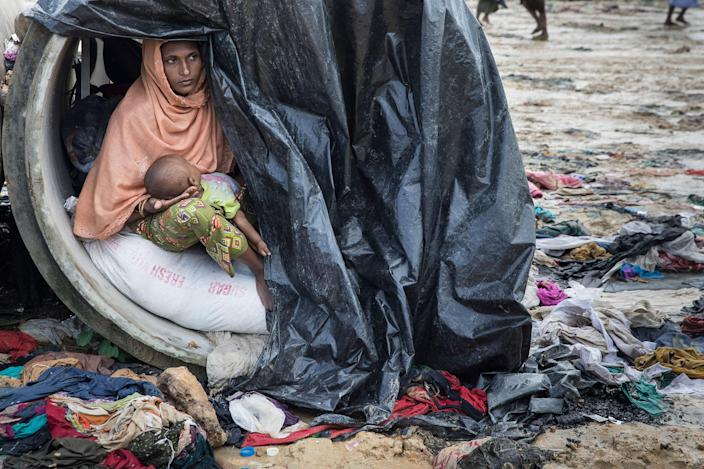 <p>Sameera, 20, looks out from a cement cylinder holding her 7 month old baby where the family are living until a shelter is built, on September 17, 2017, in Kutupalong, Cox's Bazar, Bangladesh. (Photograph by Paula Bronstein/Getty Images) </p>