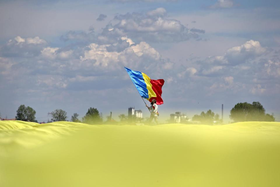 A man holding a Romanian flag stands at the edge of a huge version of the flag, on the Clinceni Airfield, south of Bucharest, Romania, Monday, May 27, 2013. Romania entered the Guinness Book of records after it unveiled the largest flag ever made. It took about 200 people several hours Monday to unfurl a five-ton flag of Romania which organizers said measured 349.4 meters by 226.9 meters, about three times the size of a football pitch.(AP Photo/Vadim Ghirda)