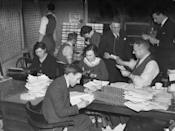<p>Journalists at Reuters Press Agency crowd around a conference table as they receive results of the general election in November 1935. Huge piles of paper and editing everything by hand was commonplace in newsrooms at the time.</p>