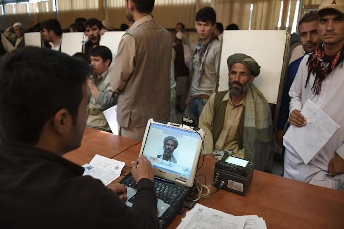An Afghan man has his photograph taken for facial biometric information as he applies for his passport in Kabul on August 25, 2015 (AFP Photo/Shah Marai)