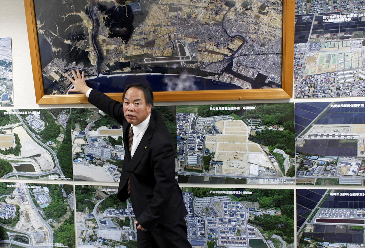 Higashi-Matsushima city major Hideo Abe shows off pictures of the city's reconstructing plan after March 11, 2011 earthquake and tsunami disaster, at the city government office in Higashi-Matsushima, northern Japan, February 22, 2017. Picture taken February 22, 2017.       REUTERS/Osamu Tsukimori