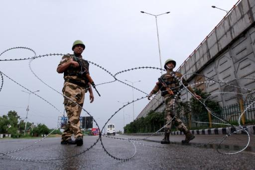 Security personnel stand guard at a roadblock on a deserted street in Jammu, Kashmir