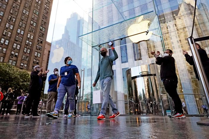 The first customer holds his iPhone 13 on its first day of sale, in New York, Friday, Sept. 24, 2021.