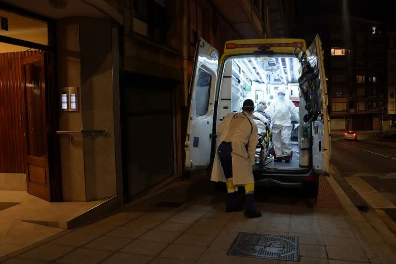 Ambuiberica medical staff members lift a suspected coronavirus disease (COVID-19) patient into an ambulance, in the Basque port town of Bermeo