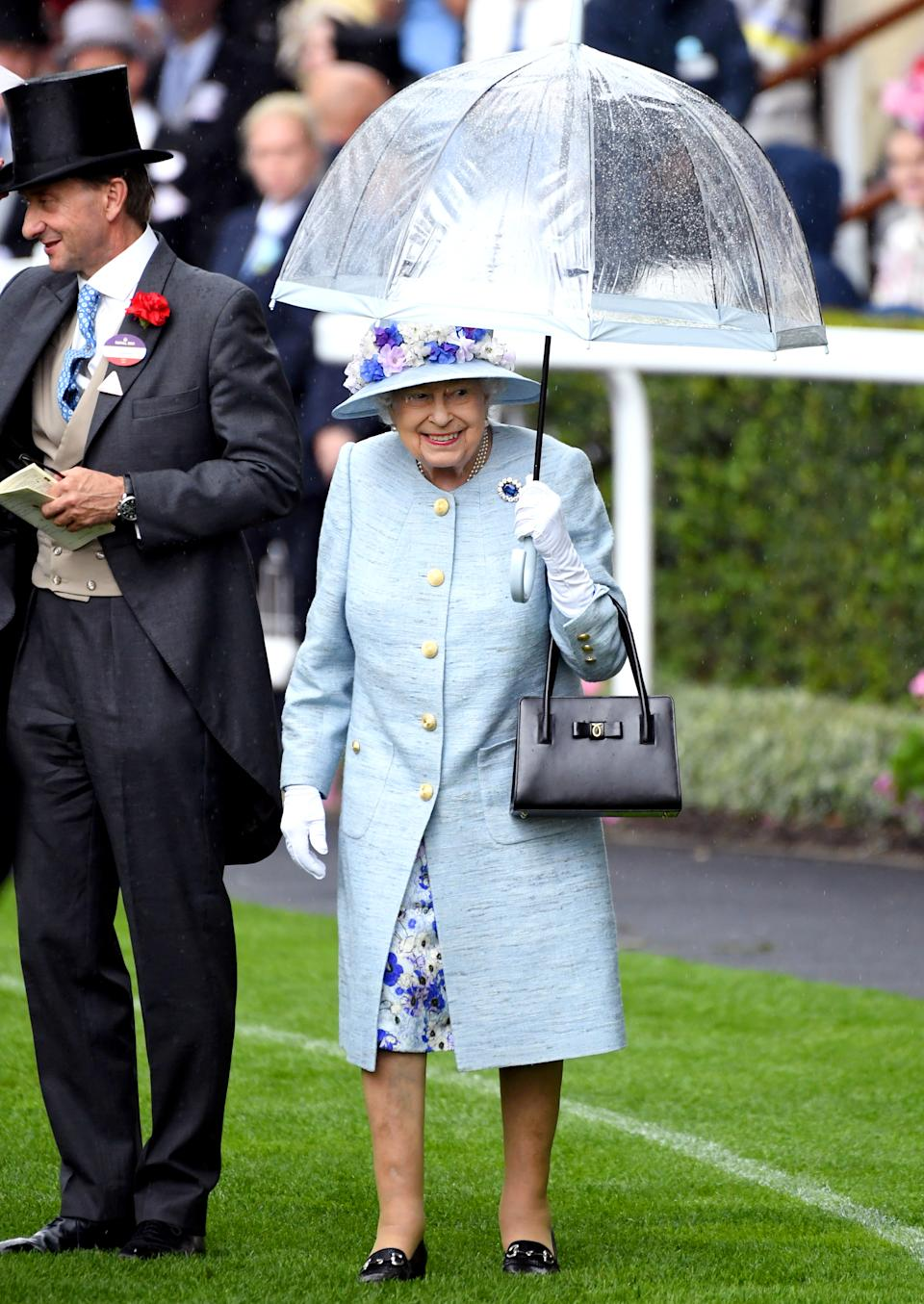 The Queen braved the rain in a mottled duck egg coat and floral dress by Stewart Parvin with a matching floral-adorned hat by milliner Rachel Trevor Morgan.<em> [Photo: PA]</em>