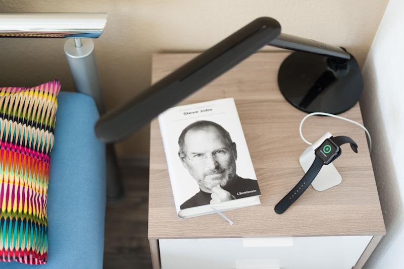 Ostfildern, Germany - May 21, 2015: An Apple Watch is being loaded on the bedside table using a stylish stand by manufacturer Spigen next to the biography of Steve Jobs, the innovative long term leader of Apple Computer Inc. The Apple smartwatch should be charged every day since the battery does not last much longer, most people use to charge their watch during night time therefore.