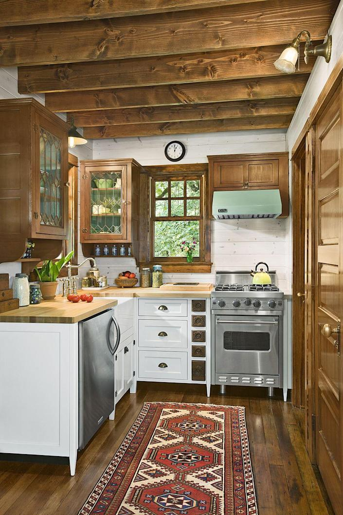 """<p>Compact appliances and smaller-scale custom cabinetry—featuring salvaged leaded fronts and old sewing drawers—are just the right size for this tiny kitchen.</p><p><a class=""""link rapid-noclick-resp"""" href=""""https://www.amazon.com/Life-Changing-Magic-Tidying-Decluttering-Organizing/dp/1607747308?tag=syn-yahoo-20&ascsubtag=%5Bartid%7C10072.g.35047961%5Bsrc%7Cyahoo-us"""" rel=""""nofollow noopener"""" target=""""_blank"""" data-ylk=""""slk:SHOP BOOKS ABOUT TIDYING"""">SHOP BOOKS ABOUT TIDYING</a></p>"""