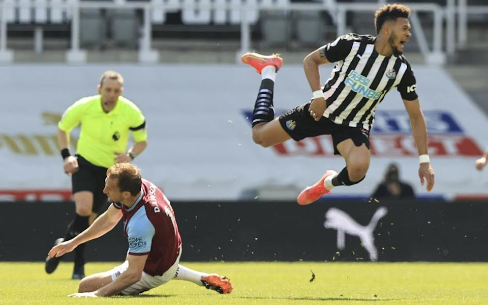 Craig Dawson (left) sends Joelinton flying – after the referee played advantage, the West Ham player received a second yellow card and was sent off.