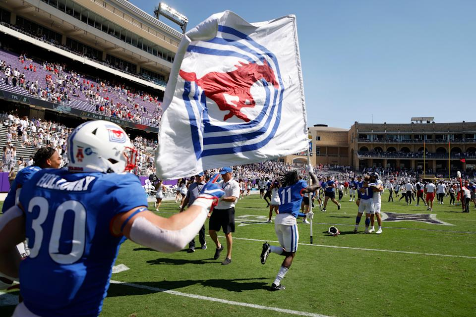 SMU wide receiver Rashee Rice (11), followed by linebacker Brian Holloway (30) runs the SMU flag to midfield after they defeated TCU.