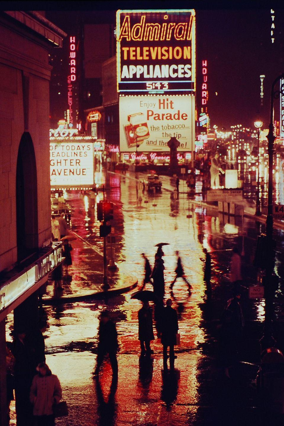 <p>The theater and billboard lights of Times Square illuminate the streets on a rainy night.</p>