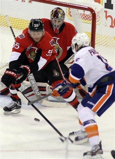 Ottawa Senators' Sergei Gonchar (55) attempts to clear the puck as Senators goaltender Craig Anderson and New Islanders' PA Parenteau (15) look on during first-period NHL hockey game action in Ottawa, Ontario, Friday Feb. 3, 2012. (AP Photo/The Canadian Press, Fred Chartrand)