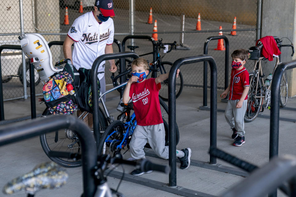 Michael Hoffman of Washington and his sons Evan, 6, center, and Andrew, 4, right, lock up their bikes as they arrive before the Washington Nationals play the Atlanta Braves in their opening day baseball game at Nationals Park, Tuesday, April 6, 2021, in Washington. (AP Photo/Andrew Harnik)