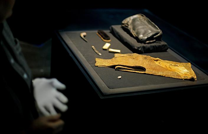 """The personal effects of William Murdoch, the bridge officer aboard the Titanic, are seen as Alexandra Klingelhofer, vice president of collections for Premier Exhibitions, Inc., takes off a white glove after handling the items before an exhibition opens to the public Tuesday, April 3, 2012, in Atlanta. From the pitch-black depths 2½ miles beneath the North Atlantic, salvagers of the Titanic made a notable discovery when they located the personal effects of Murdoch, the bridge officer who tried in vain to keep the doomed ship from colliding with an iceberg. The artifacts, including a shoe brush, straight razor and pipe, are the first to be specifically to Murdoch, a central figure in the disaster who gained added notoriety after James Cameron's polemical portrayal of him in the 1997 blockbuster movie """"Titanic."""" (AP Photo/David Goldman)"""