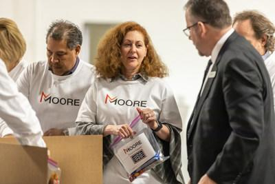To celebrate joining the Richmond community Moore executives assemble care packages for local USO.