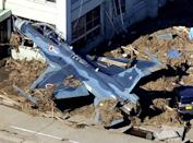 A Japanese military plane has its nose struck in a building at Matsushima air base of the Japan Air Self-Defense Force, northeastern Japan, on Saturday, March 12, 2011, one day after a giant quake and tsunami struck the country's northeastern coast. (AP Photo/Kyodo News)