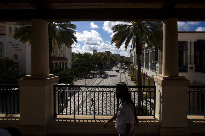 Pedestrians walk through a mostly empty shopping area in West Palm Beach, Fla., March 14, 2020. (Saul Martinez/The New York Times)