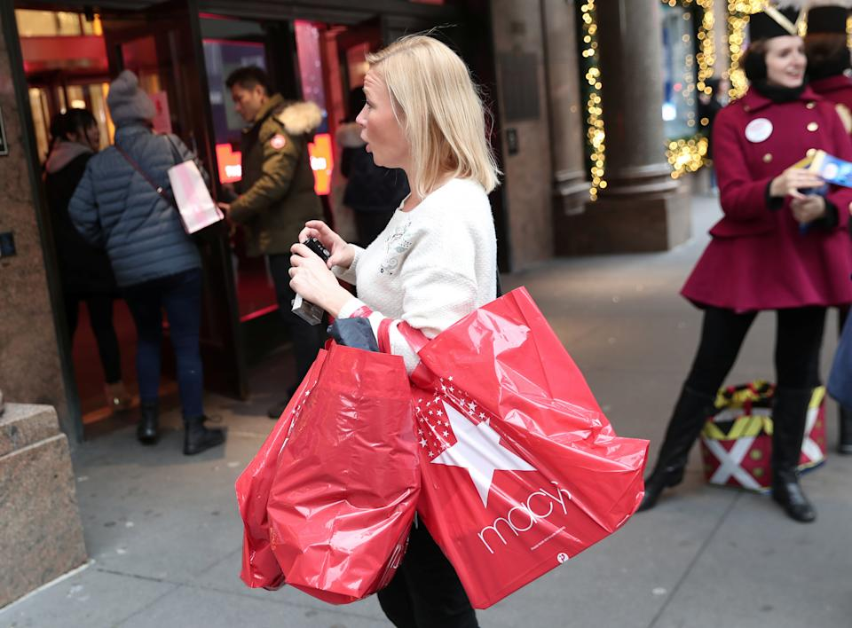 A woman stands with shopping bags outside Macy's department store in New York, U.S., December 3, 2018. REUTERS/Shannon Stapleton
