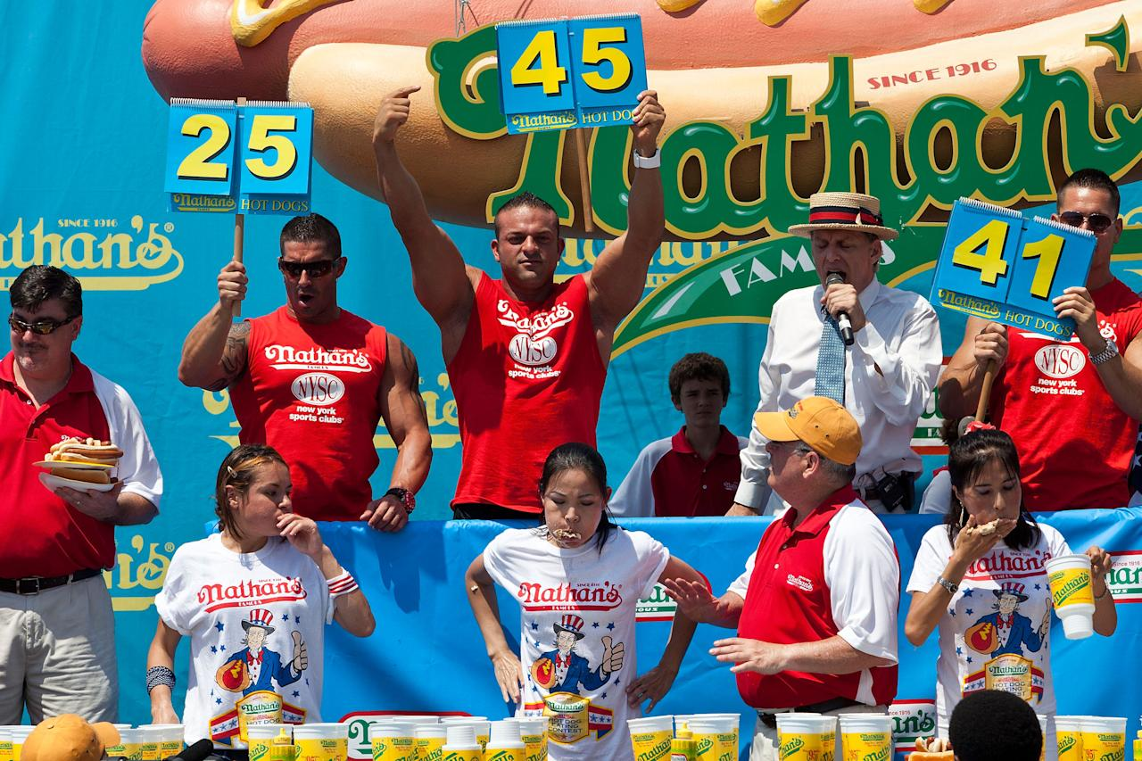Competitive eater Sonya Thomas, center on the bottom row, rests moments after the women's division of the Nathan's Famous International Hot Dog Eating Contest finishes at Coney Island on July 4, 2012 in the Brooklyn borough of New York City. Thomas won the women's division by successfully eating 45 hot dogs in 10 minutes, setting a new world record.  (Photo by Andrew Burton/Getty Images)
