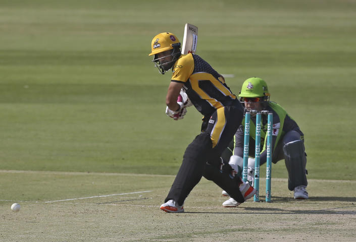 Peshawar Zalmi Ravi Bopara, left, plays a shot while Lahore Qalandars wicketkeeper Ben Dunk watches during a Pakistan Super League T20 cricket match between Peshawar Zalmi and Lahore Qalandars at the National Stadium, in Karachi, Pakistan, Sunday, Feb. 21 2021. (AP Photo/Fareed Khan)