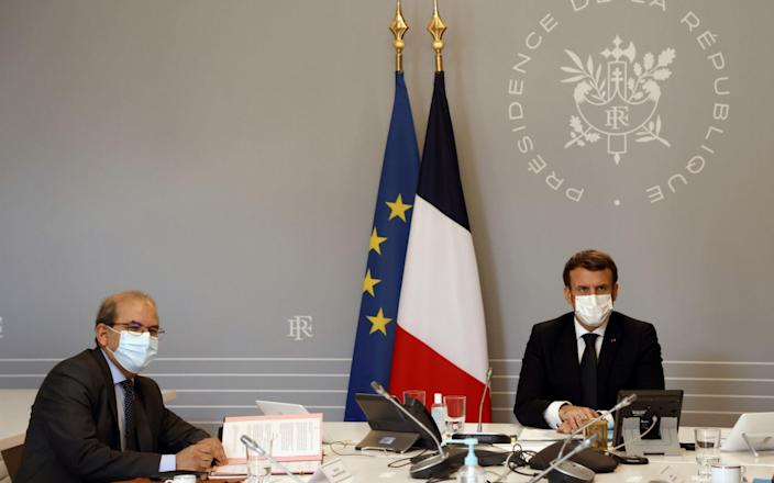 """Mohammed Moussaoui, president of the French Council of the Muslim Faith (L) signs the """"Charter of principles"""" next to French President Emmanuel Macron (R) - POOL/REUTERS"""