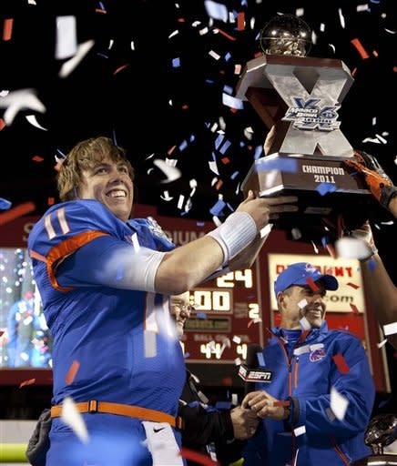 Boise State quarterback Kellen Moore (11) holds up the trophy after Boise State beat Arizona State 56-24 in the Maaco Bowl NCAA college football game, Thursday, Dec. 22, 2011, in Las Vegas. In the background is Boise State coach Chris Petersen. (AP Photo/Julie Jacobson)