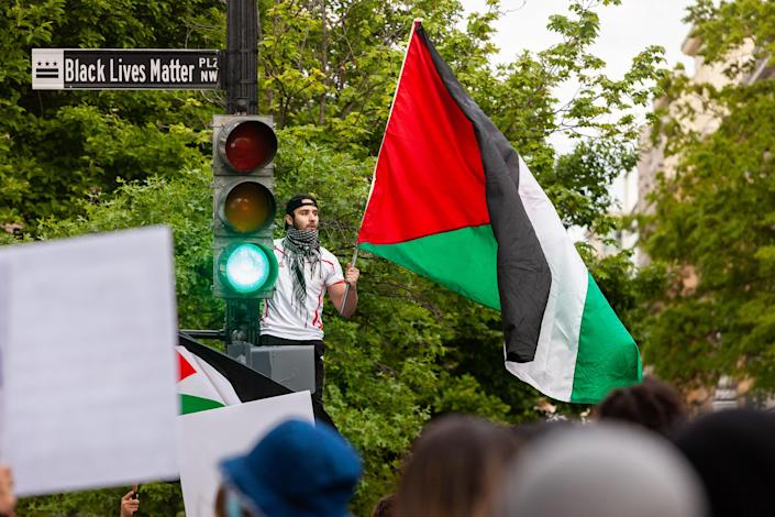 """A man waves a Palestinian flag near the White House during a protest on May 11, 2021. Democratic Congresswoman Rashida Tlaib, who is of Palestinian descent, compared the Palestinian struggle to how Black Americans have risen up against police brutality in the past year.<span class=""""copyright"""">Allison Bailey—Shutterstock</span>"""
