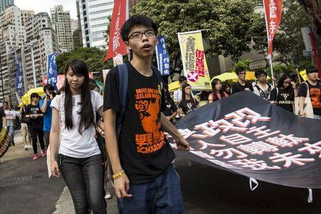 Student leader Joshua Wong (C) chants slogans during a march to demand lawmakers reject a Beijing-vetted electoral reform package for the city's first direct chief executive election in Hong Kong, China June 14, 2015. REUTERS/Tyrone Siu