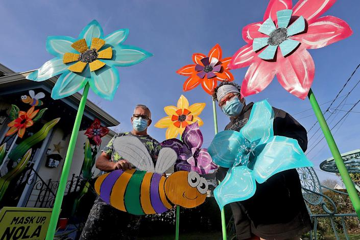 "Artists Bill Tucker, left, and Re Howse pose with their flowers and bee creations in Taylor's yard in Algiers as New Orleanians create ""house floats"" to celebrate the Carnival season after the pandemic canceled the traditional parades."