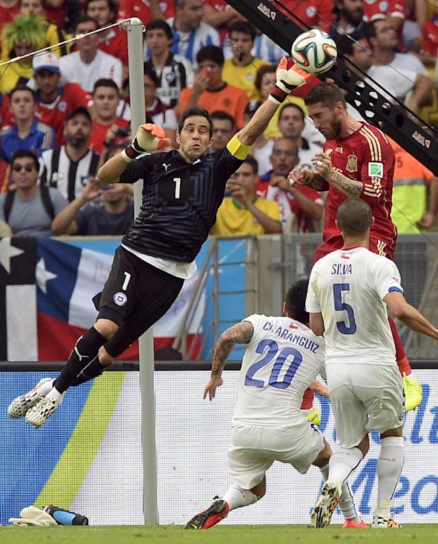 Chile's goalkeeper Claudio Bravo, left, clears the ball from Spain's Sergio Ramos during the group B World Cup soccer match between Spain and Chile at the Maracana Stadium in Rio de Janeiro, Brazil, Wednesday, June 18, 2014
