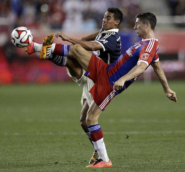 Chivas' Patricio Araujo, left, and Bayern Munich's Robert Lewandowski compete for the ball during the second half of an international friendly soccer match at Red Bull Arena, Thursday, July 31, 2014, in Harrison, N.J. Bayern Munich won 1-0. (AP Photo/Julio Cortez)