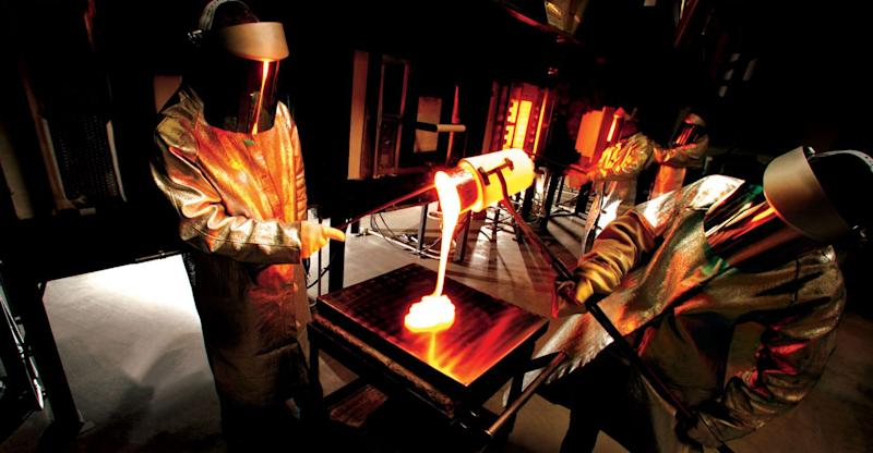 Corning scientists pouring molten glass onto a tray
