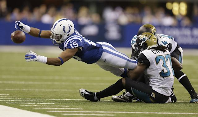 Indianapolis Colts' LaVon Brazill (15) dives to get out of bounds as he is tackled by Jacksonville Jaguars' Johnathan Cyprien (37) and Will Blackmon (24) during the first half of an NFL football game on Sunday, Dec. 29, 2013, in Indianapolis. (AP Photo/Michael Conroy)