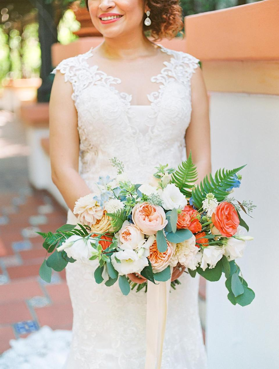 <p>Ana's oblong garden-style bouquet was filled with a myriad of rose types, dahlias, peonies, scabiosa, delphinium, and larkspur in various shades of white, ivory, peach, orange, and coral—with pops of light blue and plenty of greenery. A silk ivory ribbon held the arrangement together.</p>