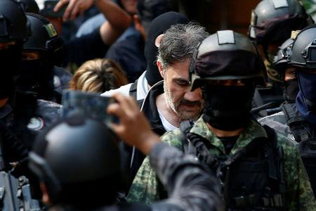 "Accused drug kingpin Damaso Lopez (C), nicknamed ""The Graduate"", is escorted by police officers after he was arrested in Mexico City, Mexico May 2, 2017. REUTERS/Carlos Jasso"