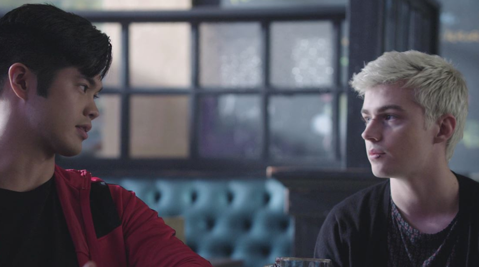 Alex Standall and Zach Dempsey stare at each other as they sit together at a restaurant table