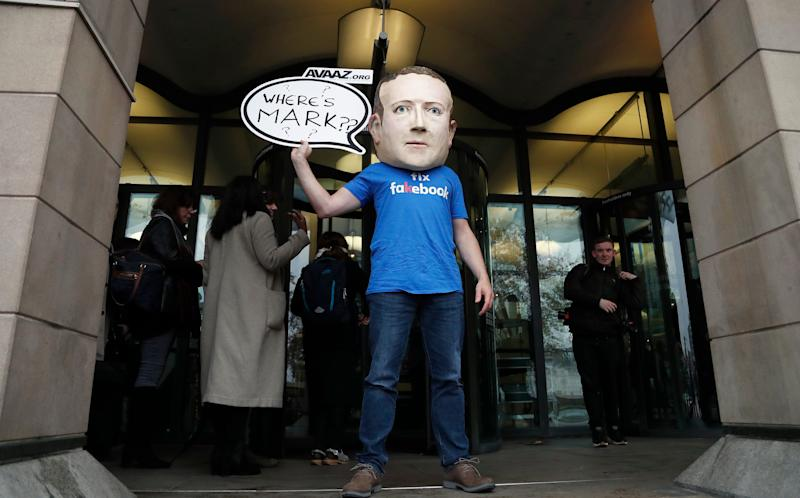 "An activist wearing a Facebook CEO Mark Zuckerberg mask stands in front of Portcullis House in Westminster as an international committee of parliamentarians met for a hearing on the impact of disinformation on democracy in London, Tuesday, Nov. 27, 2018. Lawmakers from nine countries grilled a Facebook executive who came in place of Zuckerberg on Tuesday as part of an international hearing at Britain's parliament on disinformation and ""fake news."" (AP Photo/Frank Augstein)"