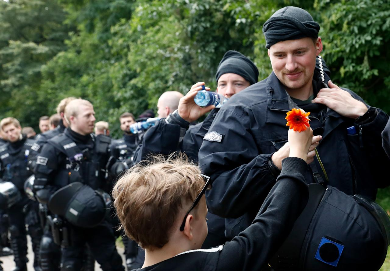 <p>A boy shows his appreciation for the police watching a demonstration pass by on July 8, 2017 in Hamburg, northern Germany as world leaders meet during the G20 summit. (Photo: Odd Andersen/AFP/Getty Images) </p>